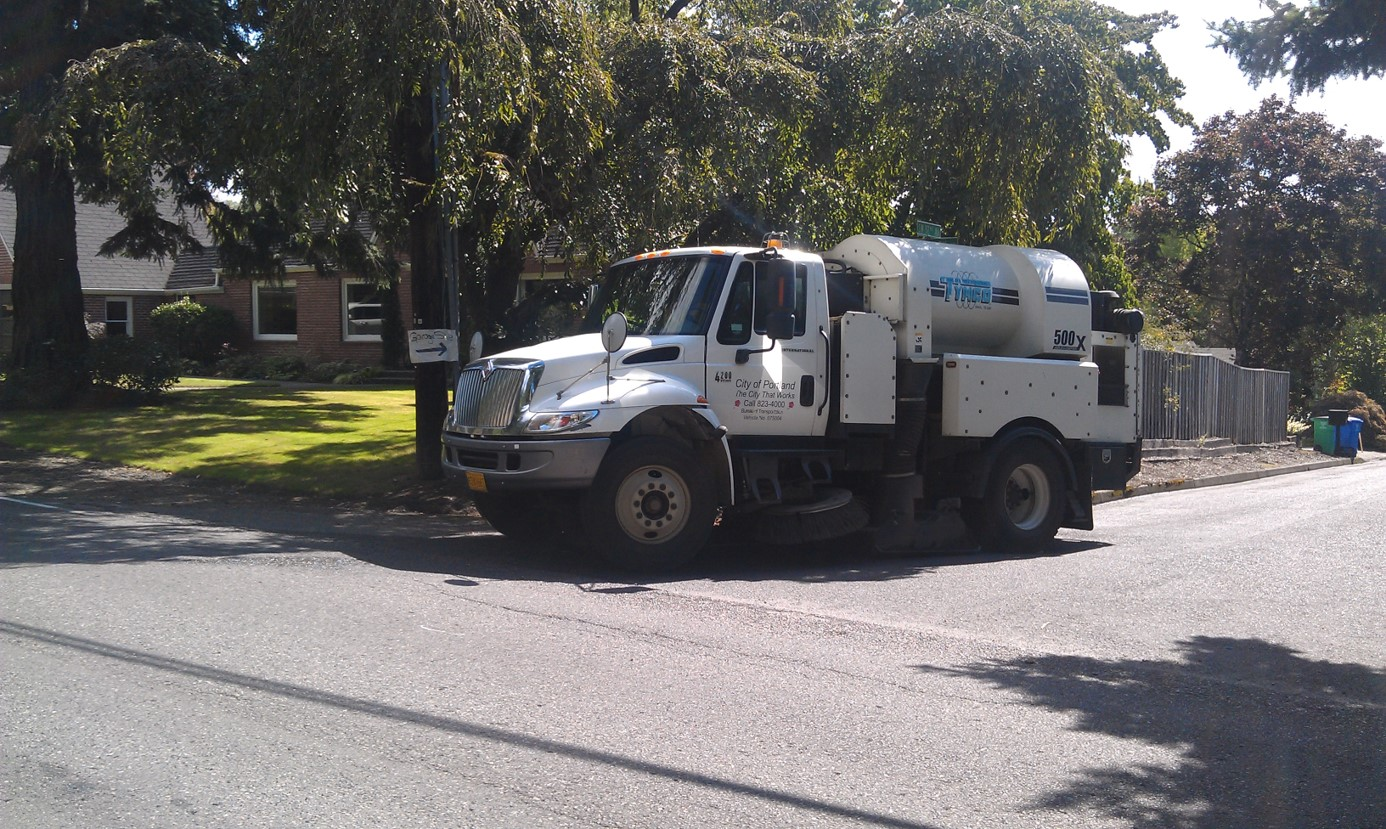 A Tymco 500x keeping the streets clean in a residential area