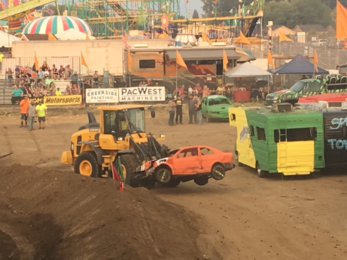 A Volvo loader clearing the field after a monster truck show