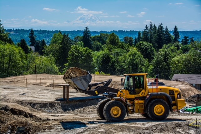 Mt. Rainier looms in the distance as a Volvo loader moves soil