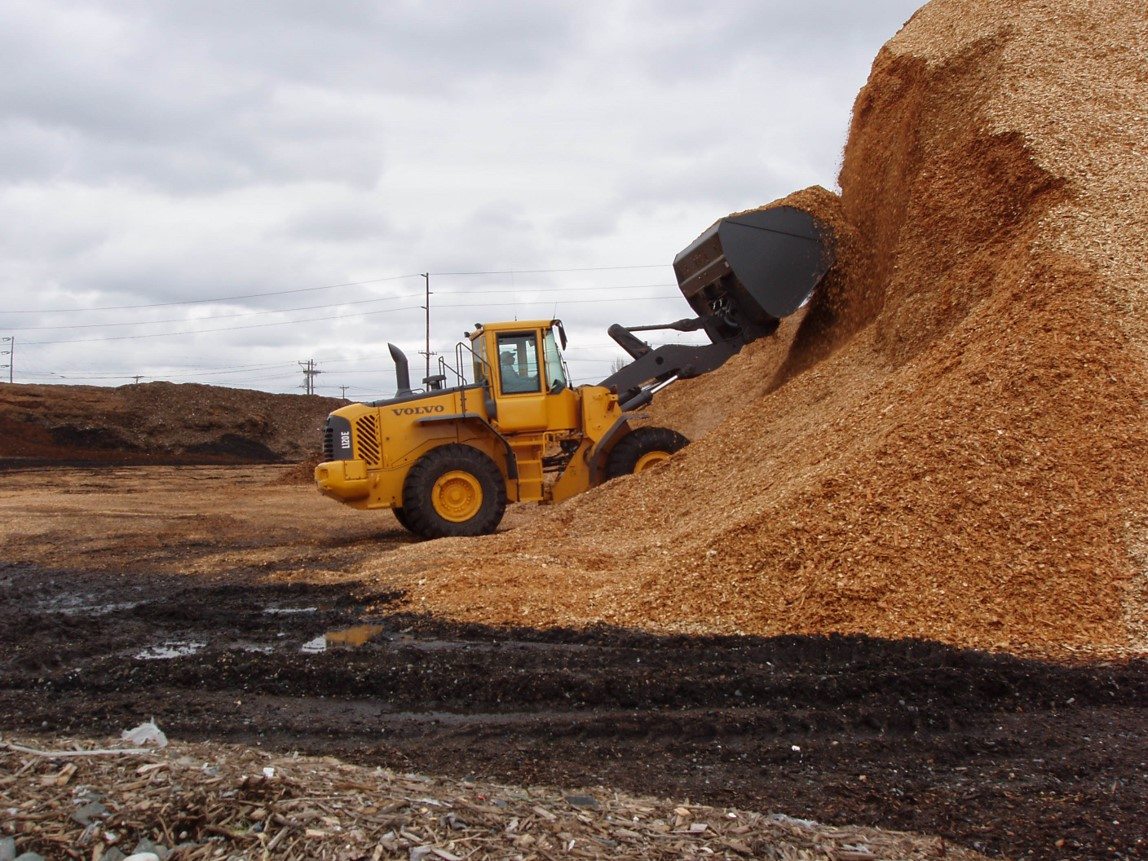 An L120E chewing up a chip pile