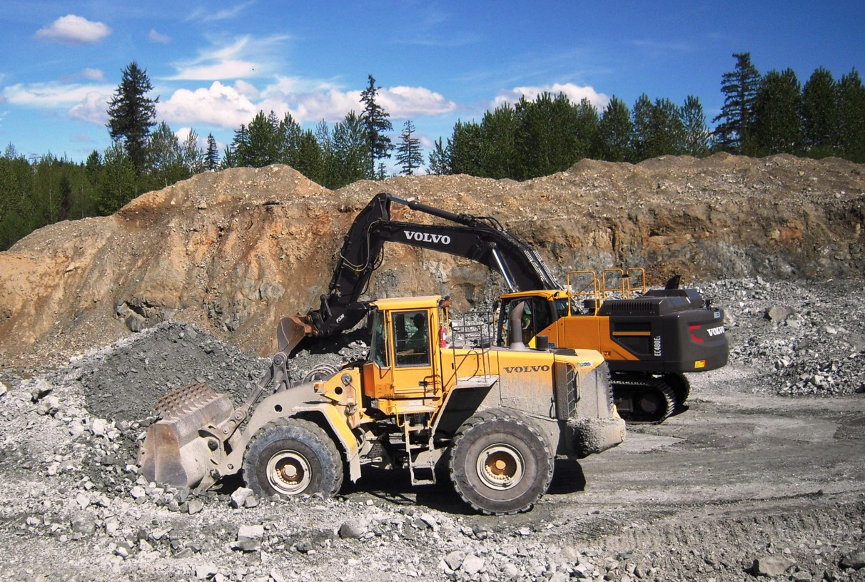 A Volvo wheel loader and excavator efficiently processing a rock pile in a Washington quarry