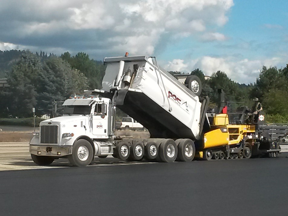 An asphalt truck delivering material to the hopper of a Volvo P7110 paver