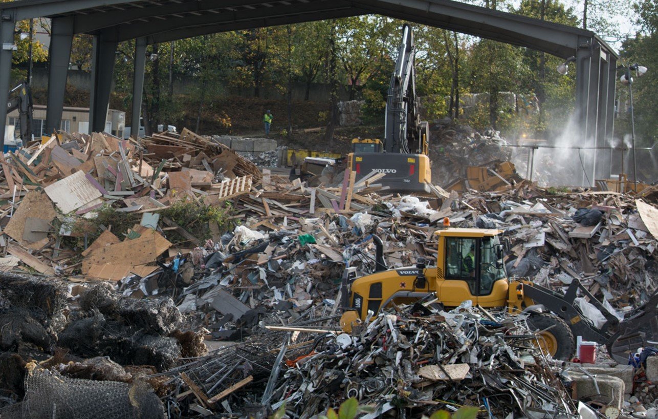 A Volvo excavator and wheel loader sorting recyclables in a Portland, OR recycling center