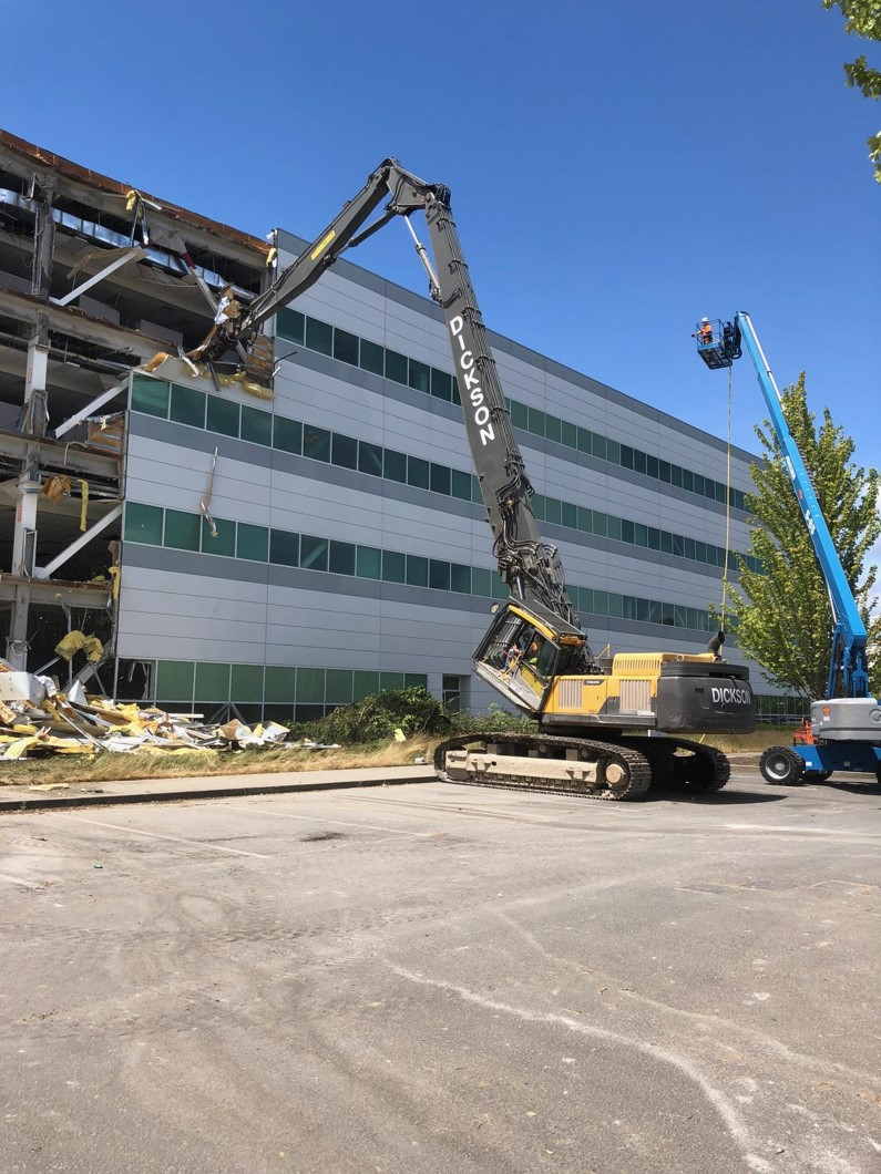 A Volvo long reach excavator with tilted cab is starting the demolition of an office building near Tacoma, WA