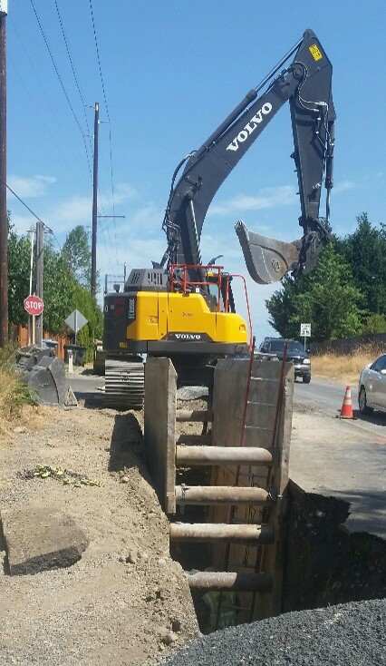 An ECR355EL trenching along a busy road