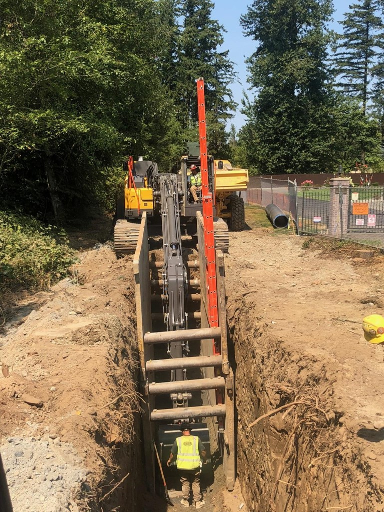 A Volvo excavator digging utility trenches in preparation for a new school in western Washington